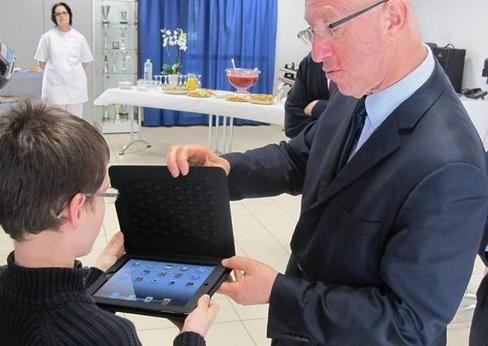 Christian Arnaud, directeur d'académie, remet une tablette à l'un des collégiens ravi.